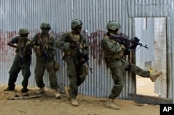 FILE - Somali soldiers search through homes for al-Shabab fighters, June, 2, 2012.