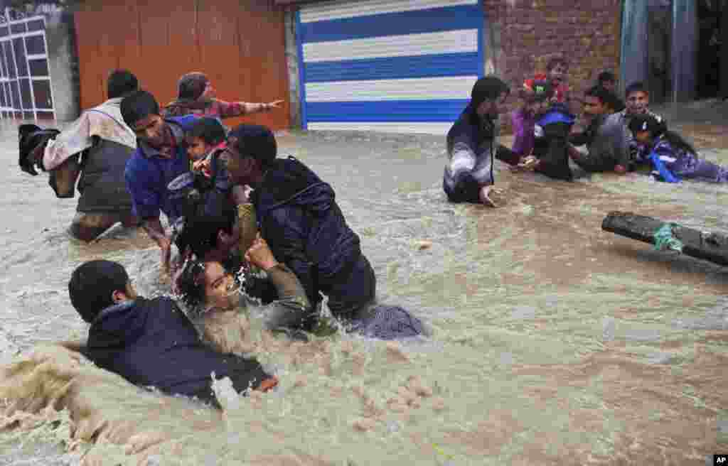 Kashmiri residents struggle to withstand sudden and strong water currents while wading through floodwaters in an effort to move to safer places in Srinagar, India.