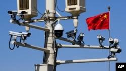 រូបឯកសារ៖ ទង់ជាតិចិនត្រូវបានដាក់នៅក្បែរបង្គោលដែលមានបំពាក់ដោយប្រព័ន្ធកាមេរ៉ាតាមដាននៅក្បែរទីលាន Tiananmen ក្នុងទីក្រុងប៉េកាំង ប្រទេសចិន កាលពីថ្ងៃទី១៥ ខែមីនា ឆ្នាំ២០២០។