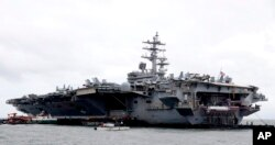 FILE - The U.S. aircraft carrier USS Ronald Reagan is anchored off Manila Bay, Philippines, for a port call, Aug. 7, 2019.