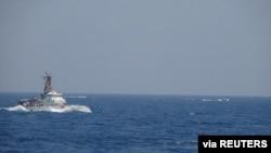 Two Iranian Islamic Revolutionary Guard Corps attack craft operate near the U.S. Coast Guard cutter Maui as it transits the Strait of Hormuz, May 10, 2021. (U.S. Navy photo)