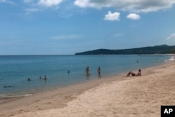 FILE - In this March 26, 2020, photo, tourists swim on a beach, Phuket, Thailand.