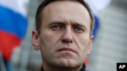 FILE - In this Feb. 29, 2020, file photo, Russian opposition activist Alexei Navalny takes part in a march in memory of opposition leader Boris Nemtsov in Moscow, Russia. Navalny has been poisoned and hospitalized on Thursday morning, Aug. 20, 2020…
