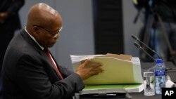 L'ancien président sud-africain Jacob Zuma examine des documents lors de sa déposition devant une commission d'État enquêtant sur de nombreuses allégations de corruption au sein du gouvernement et d'entreprises appartenant à l'État, à Johannesburg, en Afrique du Sud, le 17 juille