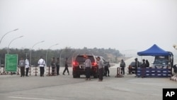 A vehicle convoy carrying a lawmaker passes through a checkpoint near the parliament building in Naypyitaw, Jan 30 2011