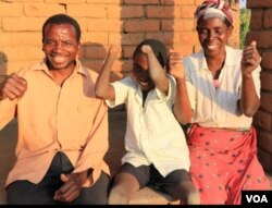 Talandira jokes around with his parents. (Lameck Masina/VOA)
