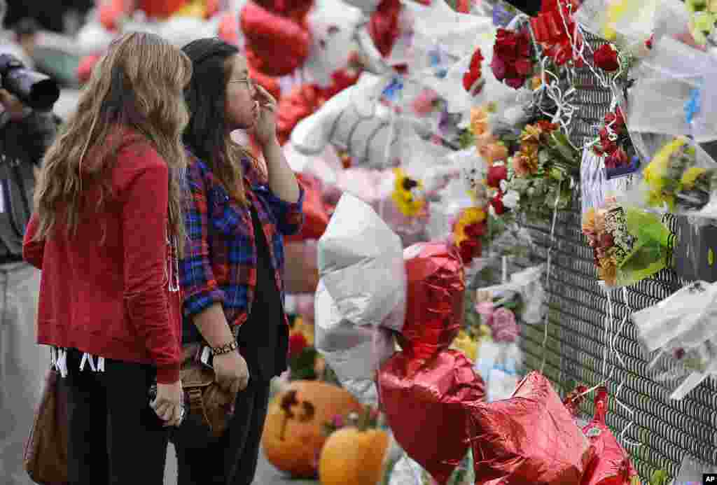 Francesca Tuazon, 17, right, and Nicole Buell, 17, view a growing memorial on a fence around Marysville Pilchuck High School, in Marysville, Washington, USA. On Oct. 24, a student opened fire in the school cafeteria, killing two fellow students before taking his own life.