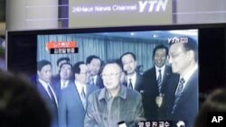 People watch file footage of North Korean leader Kim Jong Il broadcast on a TV screen in the Seoul train station in Seoul, South Korea. South Korean news agencies reported that Kim Jong Il traveled Friday to his country's key ally and benefactor China, Ma
