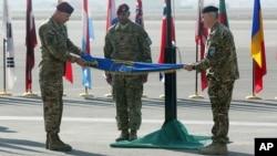 El comandante Joseph Anderson (izquierda) dobla la bandera de la coalición extranjera en Afganistan, luego de arriar su bandera para poner fin a la misión de combate en ese país.