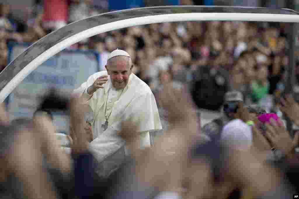 Papa Francis pozdravlja vjernike okupljene na putu do nadbiskupske palate u Rio de Janeiru.