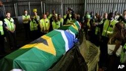 Les autorités gouvernementales, les médias et les proches entourent les cercueils, drapés dans les drapeaux sud-africains, des restes du couple Khoisan Klaas et Trooi Pienaar retournés d'Autriche, à l'aéroport international Or Tambo à Johannesburg, 20 avr