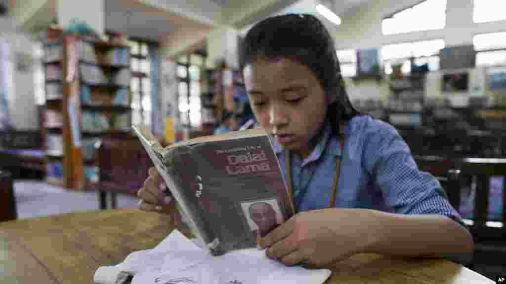 Un enfant de 9 ans Tenzin Choenyi, réfugié tibétain, lit une biographie de son chef spirituel le Dalaï Lama dans une école du village à Dharamsala, en Inde, le 20 juin 2016.
