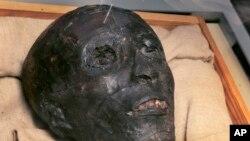 Bagian wajah mumi Raja Tut dalam kotak kaca di Mesir.