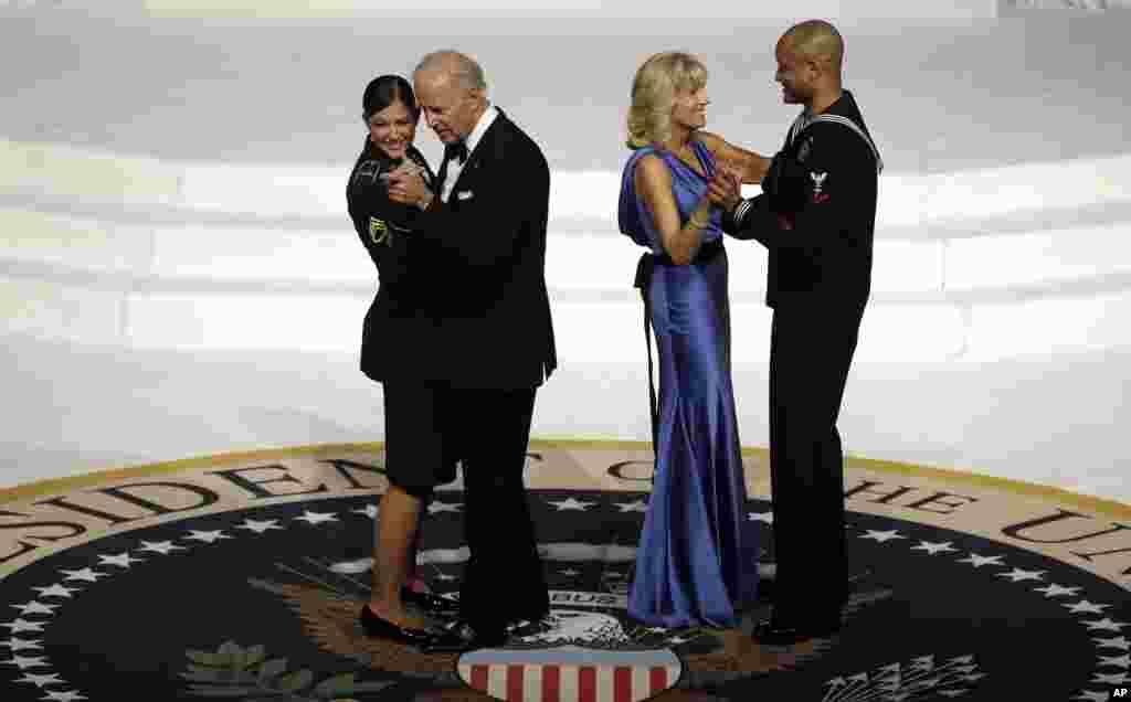 Wakil Presiden Joe Biden berdansa dengan staf Angkatan Darat Sersan Keesha Dentino, sementara istrinya Jill Biden berdansa dengan anggota Angkatan Laut Koptu Patrick Figueroa dalam pesta dansa inaugurasi Komandan Tertinggi Militer (21/1).
