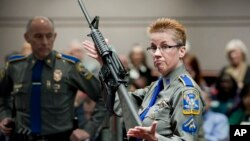 FILE -Firearms training unit Detective Barbara J. Mattson, of the Connecticut State Police, holds a Bushmaster AR-15 rifle, the same make and model used by Adam Lanza in the 2012 Sandy Hook School shooting, in this Jan. 28, 2013 photo.