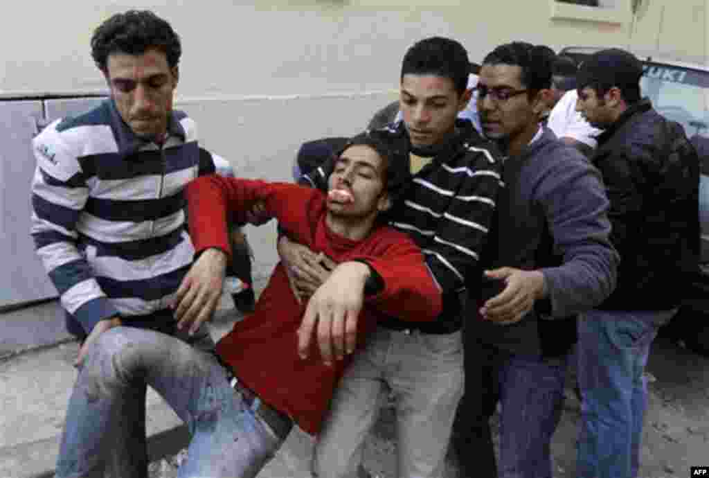 Anti-government protestors evacuate a wounded man during clashes in Cairo, Egypt, Thursday, Feb. 3, 2011. Egypt's prime minister apologized for an attack by government supporters on protesters in a surprising show of contrition Thursday, and the governmen
