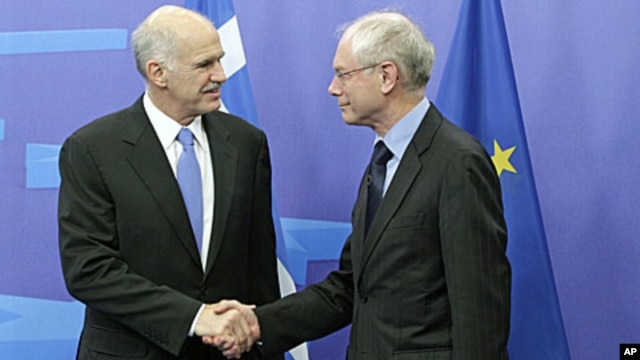European Council President Herman Van Rompuy, right, welcomes Greek Prime Minister George Papandreou at the European Council building in Brussels, June 20, 2011