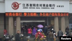 People gather in front of a branch of Jiangsu Sheyang Rural Commercial Bank, in Yancheng, Jiangsu province, March 25, 2014.