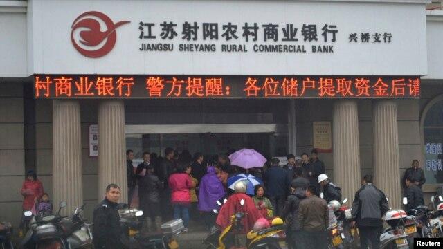 People gather in front of a branch of Jiangsu Sheyang Rural Commercial Bank, in Yancheng, Jiangsu province, March 25, 2014.