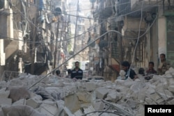 FILE - People inspect a site hit by an airstrike in the rebel held area of Aleppo's al-Sukari district, Syria, May 30, 2016.