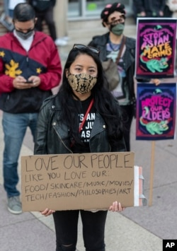 """People participate at a rally """"Love Our Communities: Build Collective Power"""" to raise awareness of anti-Asian violence outside the Japanese American National Museum in Little Tokyo in Los Angeles Saturday, March 13, 2021."""