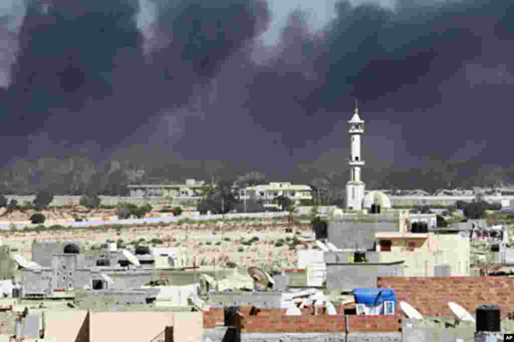 Smoke rises above downtown Tripoli following fighting at Bab Al-Aziziya compound August 23, 2011