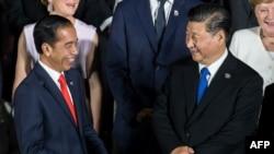 Presiden Joko Widodo berbincang dengan Presiden China Xi Jinping saat foto bersama pada KTT G20 di Osaka, 28 Juni 2019. (Foto: AFP)