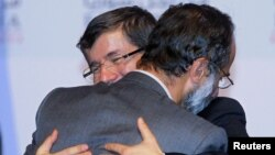 ترک وزیر خارجہ شام کی حزب اختلاف کی اتحادی کونسل کے سربراہ معاذ الخطیب کو مبارک باد پیش کررہے ہیں۔
