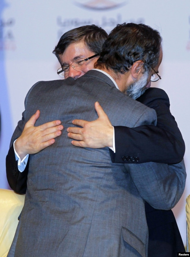 Turkish FM Ahmet Davutoglu congratulates new Syrian National Coalition head Mouaz al-Khatib during the Meeting of the General Assembly of the Syrian National Council in Doha, Qatar, November 11, 2012.