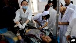 22일 중국 간쑤성 딩시 시 지진 피해자들을 의료진이 응급처치하고 있다.