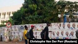 Pessoas passeiam pelas ruas cujos muros têm cartazes de campanha colados. 21 Novembro 2019