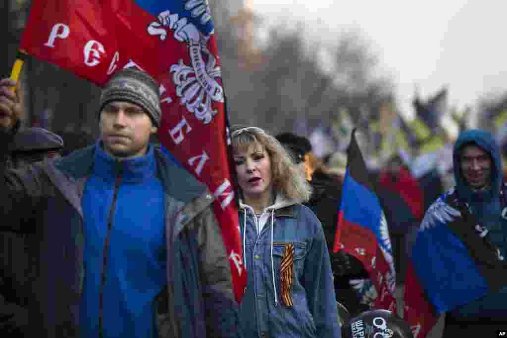 """Những người Nga chủ trương dân tộc mang cờ của """"Cộng hòa Nhân dân Donetsk"""" trong một cuộc diễu hành ủng hộ phe ly khai thân Nga chiến đấu với lực lượng chính phủ Ukraine ở miền đông Ukraine ở Moscow đánh dấu Ngày Nhân dân Thống nhất, một ngày lễ ở Nga."""