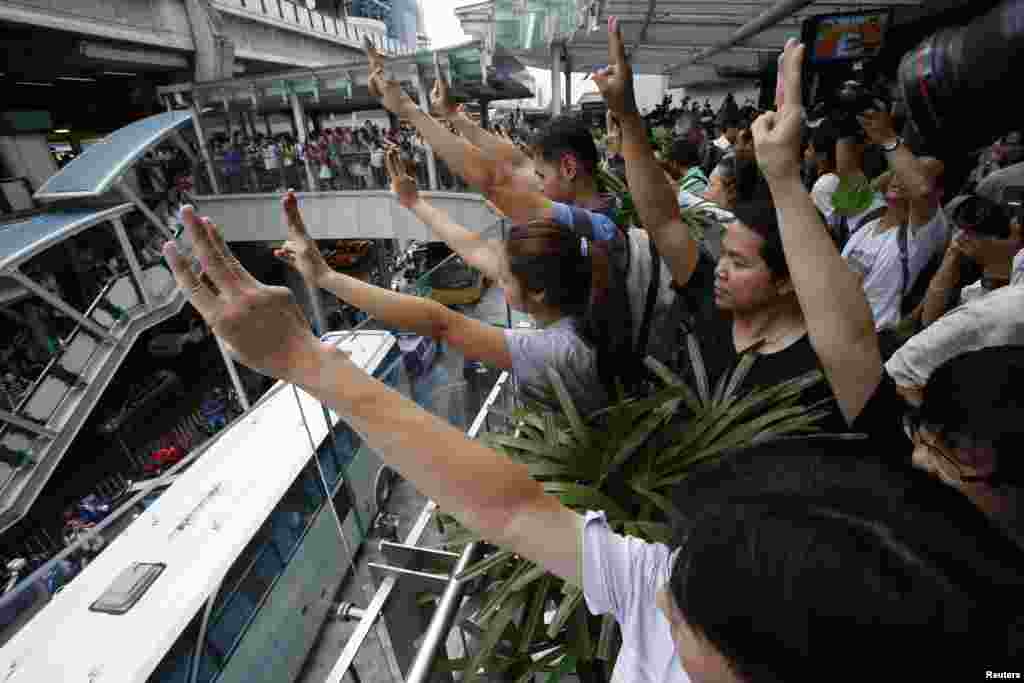 Protesters against military rule gesture by holding up their three middle fingers in the air, during a brief demonstration at a shopping mall in Bangkok, June 1, 2014.