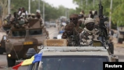 FILE - Chadian soldiers drive in retaken town of Damasak, Nigeria, March 18, 2015.