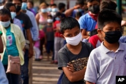 FILE - Children and adults wait in lines for donated food at a makeshift camp for migrants near the U.S.-Mexico border, May 14, 2021, in Reynosa, Mexico.