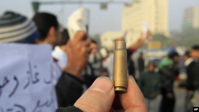 An Egyptian protester shows a spent cartridge casing during a demonstration at Tahrir Square in Cairo, December 19, 2011.