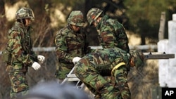 South Korean marines work for restorations of its base damaged by North Korean artillery shelling, at a military base on Yeonpyeong Island November 27, 2010. North Korea fired shells at the island off the peninsula's west coast on Tuesday, killing two civ