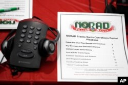 A playbook sits next to a telephone set up in the NORAD Tracks Santa center at Peterson Air Force Base, Monday, Dec. 23, 2019, in Colorado Springs, Colo. More than 1,500 volunteers will handle an estimated 140,000 telephone calls from children and their parents who will be checking on the wherabouts of Santa Claus on Christmas Eve. (AP Photo/David Zalubowski)