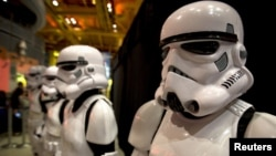 "FILE - People dressed as Storm Trooper characters from ""Star Wars"" await people to purchase toys that are to go on sale at midnight in advance of the film ""Star Wars: The Force Awakens"" in Times Square in the Manhattan borough of New York."