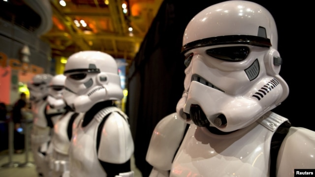 """FILE - People dressed as Storm Trooper characters from """"Star Wars"""" await people to purchase toys that are to go on sale at midnight in advance of the film """"Star Wars: The Force Awakens"""" in Times Square in the Manhattan borough of New York."""