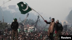 A supporter of Tahir-ul Qadri waves a Pakistani flag as he walks on a container on the third day of protests in Islamabad, Pakistan, January 16, 2013.