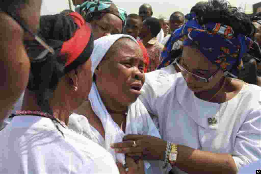 An Unidentified woman, centre, who lost her husband Mourns during a mass funeral of those killed in a Christmas Day bombing at a Catholic church in Madalla, Nigeria, on Wednesday, Feb. 1, 2012.