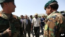 Ali Haidar Gilani son of a former Pakistani prime minister, right, walk with Pakistan Ambassador Abrar Hussain, left, as he arrives at the Ministry of Defense in Kabul, Afghanistan, Wednesday, May, 11, 2016.