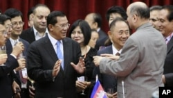 Mushahid Hussain Sayed of Pakistan, secretary-general of Centrist Democrats International Asia Pacific, right, confers with Cambodia's Prime Minister Hun Sen, center left, during a signing ceremony in Cambodia's capital Phnom Penh, Wednesday, Dec. 1, 2010