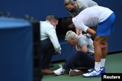 Novak Đoković (desno) stoji pored linijske sudije koju je nenamerno pogodio lopticom u grlo, 6. septembra 2020. (Credit: Danielle Parhizkaran-USA TODAY Sports)
