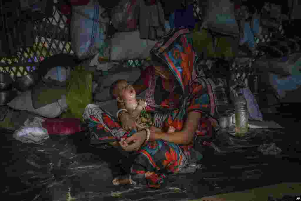 A Hindu woman, who crossed over from Myanmar into Bangladesh, holds her baby as she sits inside a refugee camp set up for Hindu refugees near Kutupalong, Bangladesh.