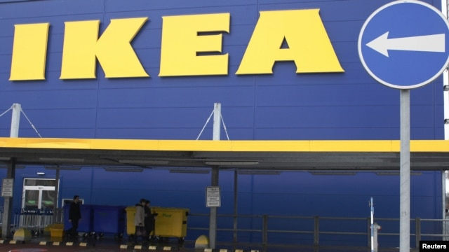 People walk alongside an IKEA outlet in Prague, Feb. 25, 2013.
