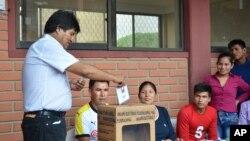 Bolivia's President Evo Morales, left, casts his ballot at a polling station in Villa 14 de Septiembre, in the Chapare region, Bolivia, Sunday, Feb. 21, 2016.