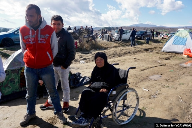 A wheelchair-bound migrant woman waits in the makeshift refugee camp in the Idomeni, Greece, near its border with Macedonia, March 4, 2016. (J. Dettmer for VOA)