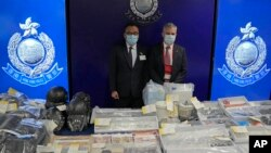 Senior Superintendent Li Kwai-wah, left, of Hong Kong Police, and senior bomb disposal officer Alick McWhirter pose with the seized evidence during a news conference at police headquarters in Hong Kong, July 6, 2021.(AP Photo/Kin Cheung)